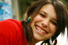 Smiling girl. Young teenager with a big smile with a graffiti wall in background Stock Images