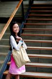 Smiling girl. Portrait of a smiling asian girl with a bag Royalty Free Stock Photos