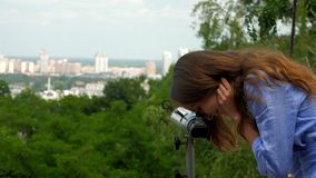 Smiling girl admires cityscate looking into grey telescope stock footage