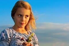 Smiling girl against the blue sky. Smiling girl with flowers against the blue sky Royalty Free Stock Image