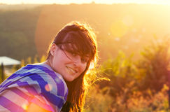 Smiling girl against sunlight Royalty Free Stock Images