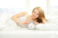 Smiling girl with alarm clock Royalty Free Stock Images