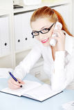 Smiling girl answering the phone and holding pen. Stock Photography