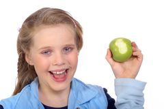 Smiling girl with an apple. Fruit is healthy and better than candy Royalty Free Stock Photo