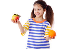Smiling girl with apple and orange Royalty Free Stock Photo