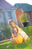 Smiling girl with apple on pumpking at garden Stock Photography