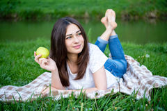 Smiling girl with an apple resting on the lawn Royalty Free Stock Image