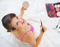Smiling girl applying makeup. Upper view Stock Photos