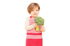 A smiling girl with apron holding a broccoli Royalty Free Stock Photo