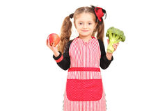 A smiling girl with apron holding a broccoli and red apple Stock Images