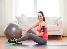 Smiling girl with armband execising at home. Fitness, sportm home and dieting concept - smiling teenage girl with armband execising at home stock images