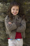 Smiling girl with arms crossed leaning against wall Stock Images