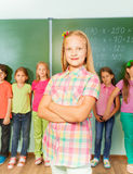 Smiling girl with arms crossed near chalkboard Royalty Free Stock Images