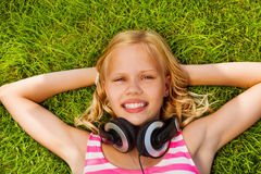 Smiling girl with arms under head wears headphones Royalty Free Stock Photography