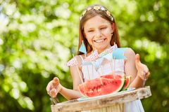 Birthday girl serves fresh watermelons. Smiling girl as a birthday girl is serving fresh watermelons Royalty Free Stock Images