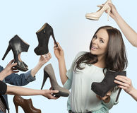 Smiling girl with assortment of shoes Royalty Free Stock Image