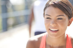 Smiling Girl. Athletic girl, smiling with a man in the background Royalty Free Stock Image