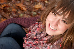 Smiling girl on the autumn ground Royalty Free Stock Photography