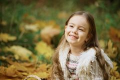 Smiling girl in autumn Leafs. Autumn activities for children. laughing girl. Little child in autumn park.  royalty free stock photos