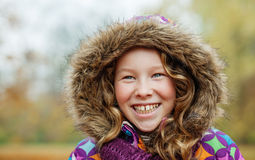 Smiling girl in an autumn park. Happily smiling teenager girl in a colorful jacket with hood Stock Images