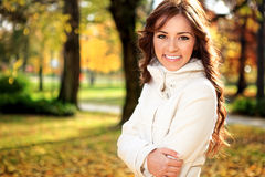 Smiling girl autumn park. Beautiful young woman in autumn park royalty free stock image