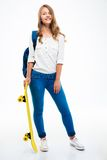 Smiling girl with backpack holding skateboard Royalty Free Stock Photos