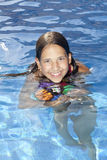 Smiling girl with ball in the swimming pool Stock Photos