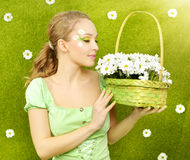 Smiling girl with a basket of flowers Royalty Free Stock Image