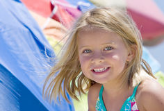 Smiling Girl at Beach. Happy smiling young girl with bright green eyes and blond hair flying in the breeze, and colorful beach umbrellas in background stock photography
