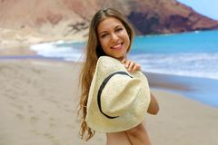 Smiling girl on the beach covering her body with a hat.  royalty free stock photo
