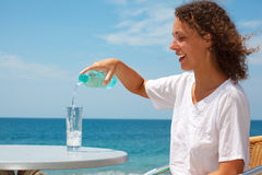 Smiling girl on beach pours water into glass Royalty Free Stock Image