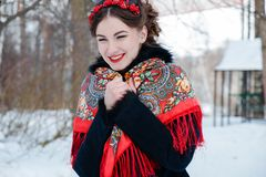 Winter portreit smiling girl with beautiful hair on her head in Russian folk style in red shawls royalty free stock photos