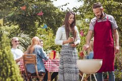 Smiling girl with beer next to friend and grill during birthday party in the garden royalty free stock photography