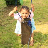 Smiling girl behind a broken swing. Smiling little girl in blue skirt and pink t-shirt holding a broken swing and looking thru Stock Photography