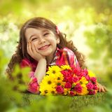 Smiling girl with big bouquet of flowers. Lying on grass. Spring, Mothers day, family holiday, Happiness concept Stock Photo