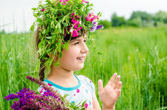 Smiling girl with big bouquet of spring flowers on green grass. Stock Photos