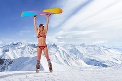 Smiling girl in bikini holding snowboard above head. Smiling unrecognizable blonde girl in bikini swimsuit with snowboard in outstretched arms above head against royalty free stock photo