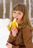 Smiling girl biting a banana Royalty Free Stock Image