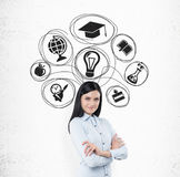 Smiling girl with black hair and education icons. Smiling girl with black hair is standing near white wall with education sketches on it. Concept of further Stock Photo