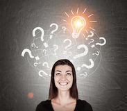 Smiling girl in black and light bulb with question marks Royalty Free Stock Photo