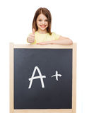 Smiling girl with blackboard showing thumbs up Royalty Free Stock Photos