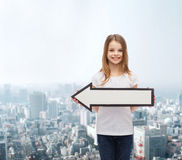 Smiling girl with blank arrow pointing left Royalty Free Stock Photos