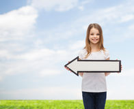 Smiling girl with blank arrow pointing left Royalty Free Stock Photo
