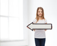 Smiling girl with blank arrow pointing left Royalty Free Stock Images