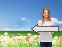 Smiling girl with blank arrow pointing left Stock Photos