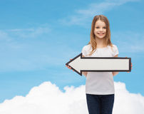 Smiling girl with blank arrow pointing left Stock Photography