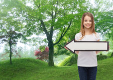 Smiling girl with blank arrow pointing left Stock Image