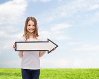 Smiling girl with blank arrow pointing right Royalty Free Stock Photos