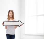 Smiling girl with blank arrow pointing right Stock Photo