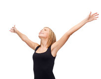 Smiling girl in blank black tank top waving hands Stock Photo